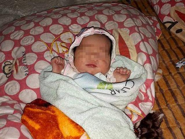 Bé gái sơ sinh quấn trong chiếc màn, bị bỏ rơi bên lề đường