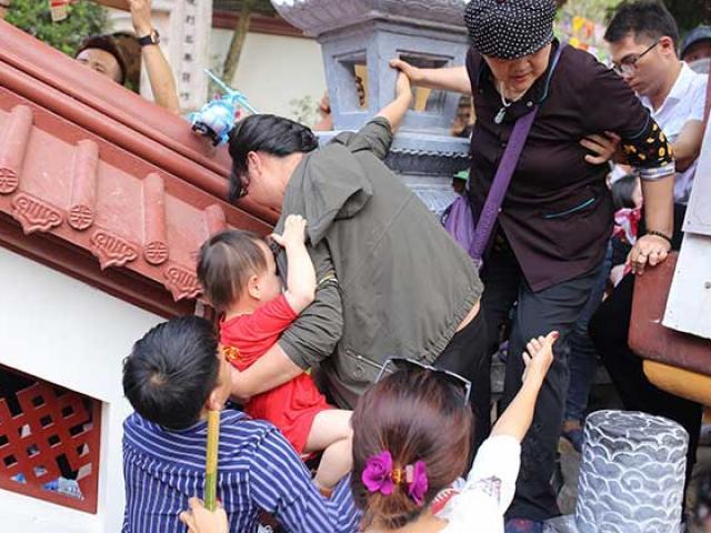 """Bế trẻ con chen lấn, """"đánh đu"""" trên tường rào vào cúng lễ ở chùa Hương"""