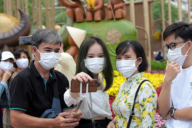 """Người dân xếp hàng đo thân nhiệt, đeo khẩu trang """"check in"""" đường hoa Tết Tân Sửu 2021 - hình ảnh 8"""