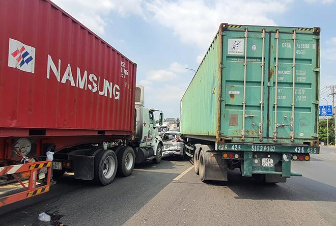 Ớn lạnh hình ảnh ô tô 7 chỗ biến dạng, bị kẹp chặt giữa 2 xe container - hình ảnh 1
