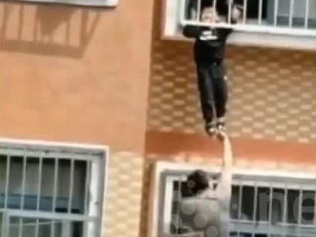 Thót tim khoảnh khắc giải cứu bé trai treo lơ lửng giữa ban công tầng 7