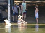 Gái xinh mặc bikini ngồi thả dáng trong nước sông đầy cá sấu