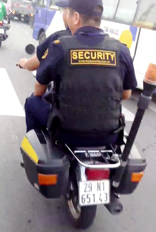 Bảo vệ giắt súng, không đội nón bảo hiểm… nghênh ngang trên đường - 1