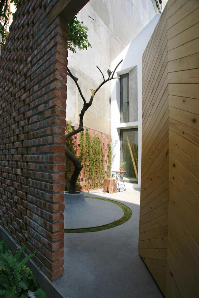 Bức tường ở cổng được xây bằng gạch thô xen kẽ, tạo thành một hàng rào thưa thớt, tách biệt căn nhà với đường phố, đồng thời chia sẻ không gian xanh với hàng xóm.