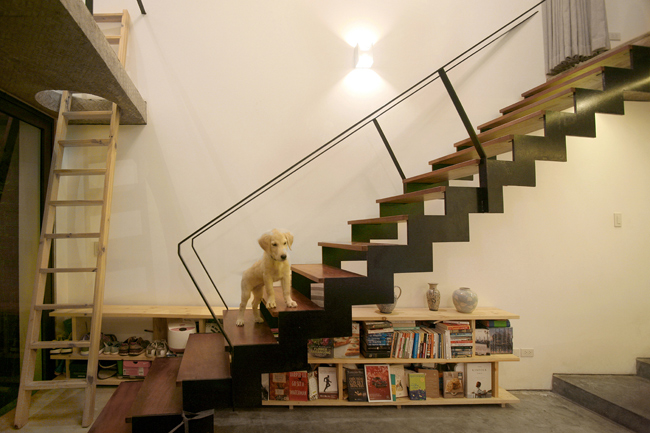 Dưới cầu thang được bố trí một giá sách nhỏ.